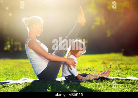 Happy young mother practicing sitting boat yoga pose with her little daughter outdoors - Stock Photo