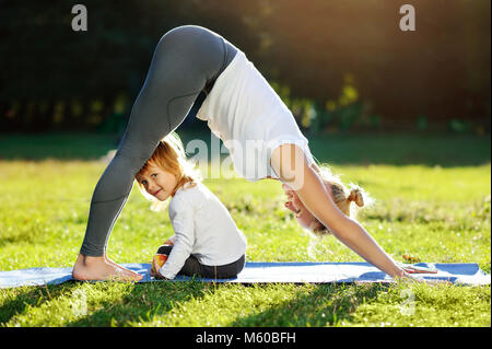 Little girl is sitting on the yoga mat while her mother practicing Downward Facing Dog yoga pose - Stock Photo