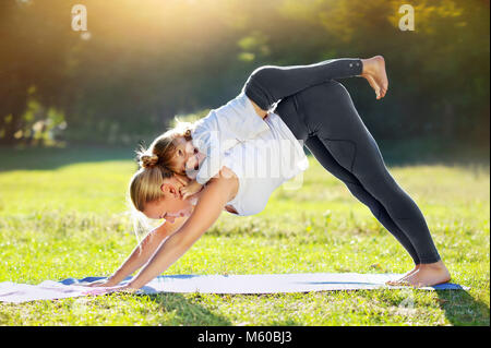 Mother practicing Downward Facing Dog yoga  Pose carrying her daughter on the back - Stock Photo