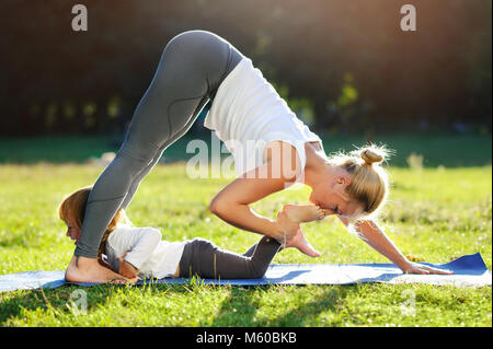 Sportive mother practicing yoga in the park and playing with daughter kissing her toes jokingly - Stock Photo