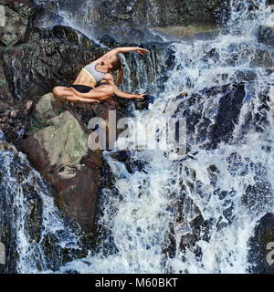 Woman practicing yoga sitting near the waterfall - Stock Photo