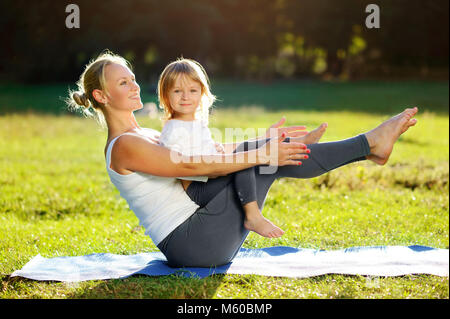 Yoga  mother practicing sitting boat yoga pose with her little daughter in the park - Stock Photo