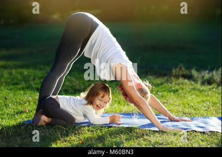 Yoga family practicing yoga in the park having fun - Stock Photo