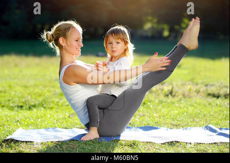 Young sportive mother playing with her little daughter while practicing boat yoga pose - Stock Photo