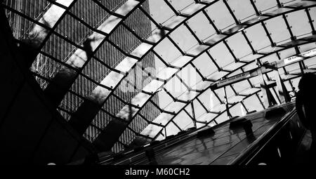 The morning sun shines through the glass roof of Canary Wharf Underground Station in east London, Britain February - Stock Photo