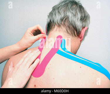 female physiotherapist applies tape on back of caucasian man - Stock Photo