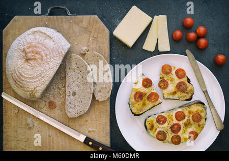 Cheese and tomatoes on toasted rye bread with a slate background - Stock Photo