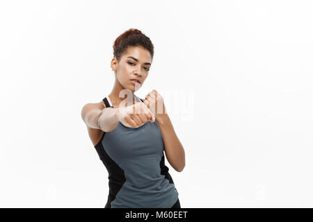Healthy and Fitness concept - portrait of African American woman punching in air with confident face. Isolated on - Stock Photo