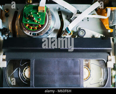 VHS tape inside a VCR player, reels moving while reading the contents. Close-up detail shot. - Stock Photo