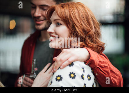 Close up shot of a millennial couple talking at a social event. - Stock Photo
