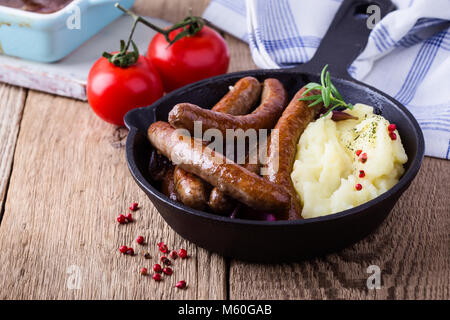 Sausage and onion casserole served with potato mash in cast iron skillet on rustic wooden table - Stock Photo