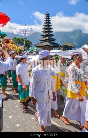 Balinese villagers participating in traditional religious Hindu procession in Ulun Danu temple Beratan Lake in Bali - Stock Photo