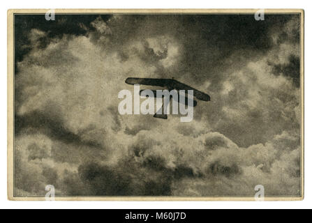 Old German postcard: 'A high-altitude flight' Silhouette of a biplane against a background of clouds. The first - Stock Photo