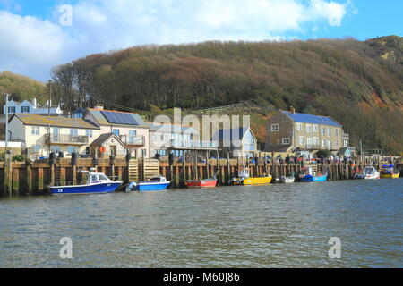 Colourful boats moored at Axmouth Harbour on the river Axe Estuary near town of Seaton in East Devon - Stock Photo