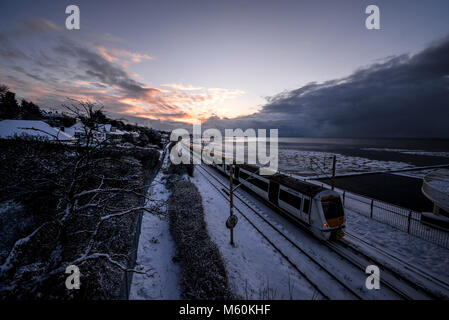 Train in snow. C2C railway train running through snow covered lines in Chalkwell near Southend on Sea, Essex at - Stock Photo