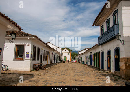 Paraty, Brazil. Cobblestone street with old houses under blue cloudy sky in Paraty, a historic town totally preserved - Stock Photo