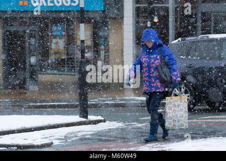 Ilkley, West Yorkshire. 27th Feb, 2018. UK Weather: A woman in Ilkley,  head bowed, dressed in winter clothing with - Stock Photo