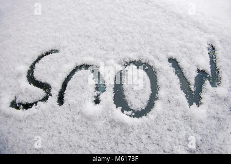 The word 'snow' written on a car windscreen covered in snow. - Stock Photo