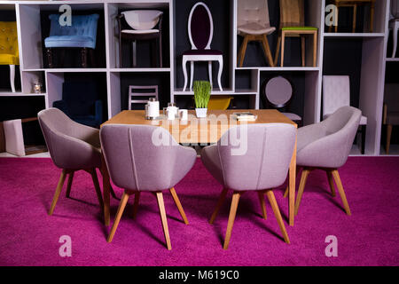Shop, sale of furniture in a shopping center. Exposition sample Dining wooden table with textile chairs in gray - Stock Photo