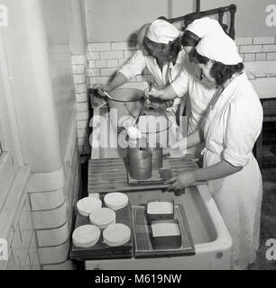 1950s, historical picture showing three young female agricultural students inside a dairy making cheese. Such hands - Stock Photo