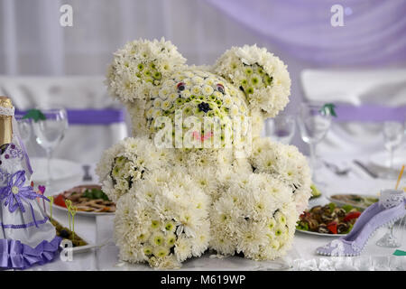 Teddy bear made of flowers on wedding table - Stock Photo