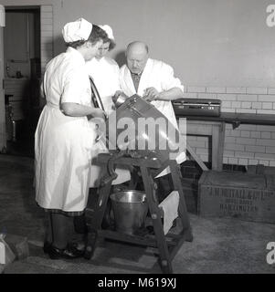1950s, historical, male teacher at a dairy factory showing two female students or apprentices, how to use the mini - Stock Photo