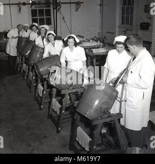1950s, historical, male teacher at a dairy showing a group of female students or apprentices how to use the mini - Stock Photo