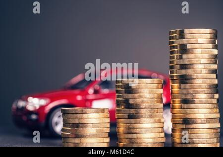 Rising piles of coins and a red car in the background   usage worldwide - Stock Photo