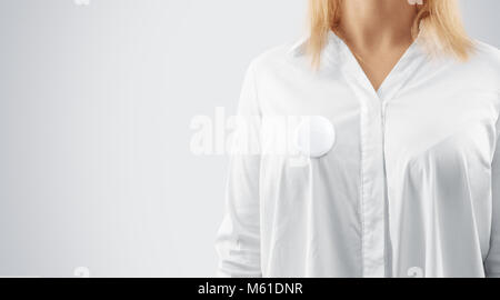 Blank button badge mockup pinned on the womans chest, close up view. Girl wear white shirt and campaign pin mock - Stock Photo