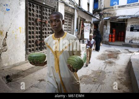 Man with a two water melons next to the massive teak doors of one house in Stone Town s maze of narrow streets, - Stock Photo