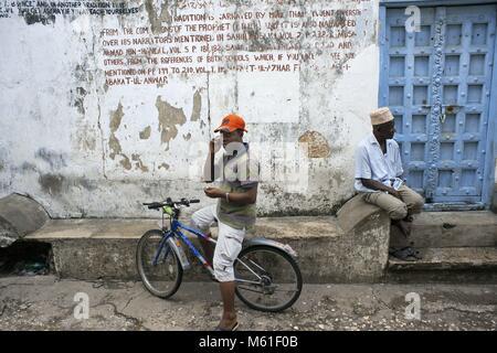 Local people and bicycle in one of Stone Town s maze of narrow streets, Zanzibar, Tanzania. | usage worldwide - Stock Photo