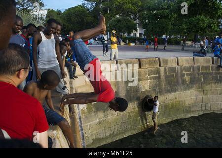 Local boys jumping off the Malecon into the sea next to the pier in Stone Town, Zanzibar, Tanzania | usage worldwide - Stock Photo