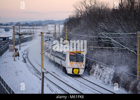 Train in snow. C2C railway train running through snow covered lines in Chalkwell near Southend on Sea, Essex during - Stock Photo