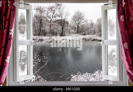 View through open window onto a beautiful frozen lake winter snow in rural England. Red curtains hang in front of - Stock Photo