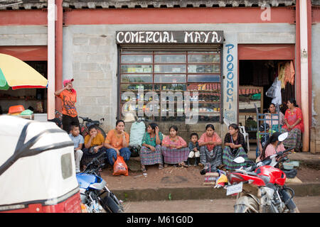 Poqomchi' Maya women and children sitting outside a shop (store) in Santa Cruz Verapaz, Alta Verapaz department, - Stock Photo