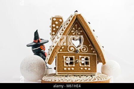 The gingerbread house with two snowball and magician. The white sky in the background. - Stock Photo