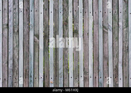 Wooden fence from thin planks, fixed by nails and screws, many knots, cracks, scratches, chips and slits on junction, - Stock Photo
