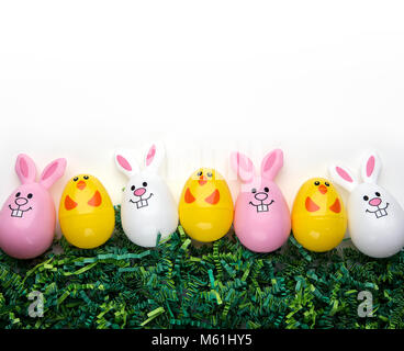 Plastic bunny and chick eggs on green grass - Stock Photo