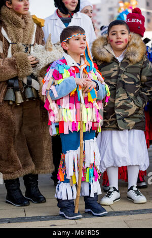 PERNIK, BULGARIA - JANUARY 26, 2018: Young male participant in colorful rag Kuker costume leans on wooden stick at the annual International Festival o