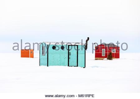 Colourful Ice Fishing shacks on Lake Winnipeg, Manitoba, Canada. - Stock Photo
