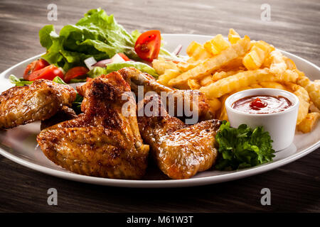Grilled chicken wings, chips and vegetables on wooden table - Stock Photo
