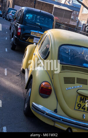 A Volkswagen Beetle original yellow coloured car next to a black cab london taxi in a back street in the capital. - Stock Photo