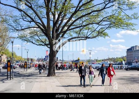 Tourists stroll at Nybroplan during springtime in Stockhom. Stockholm is a major travel destination. - Stock Photo