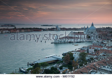 A colorful sunset over the Roman catholic church, Santa Maria della Salute with the Grand Canal. - Stock Photo