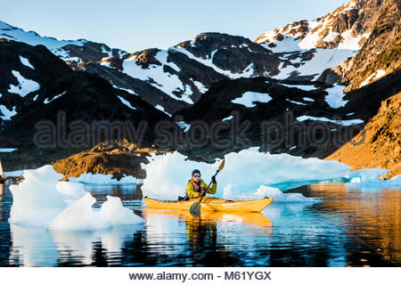 A woman kayaking through icebergs beneath snowcapped mountains in a fjord. - Stock Photo