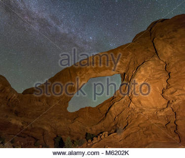Milky Way above Arch Window against starry sky at night in Arches  National Park. - Stock Photo
