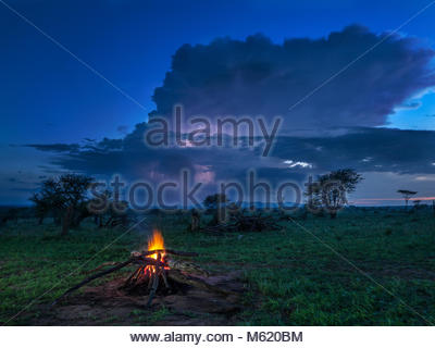 A campfire burns in early evening with storm behind. - Stock Photo