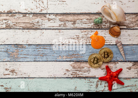 Two golden bitcoins with seashells and starfish on vintage wooden table top view - Stock Photo