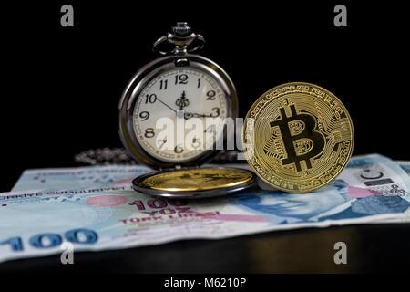 Standing golden bitcoin and pocket watch on turkish lira - Stock Photo