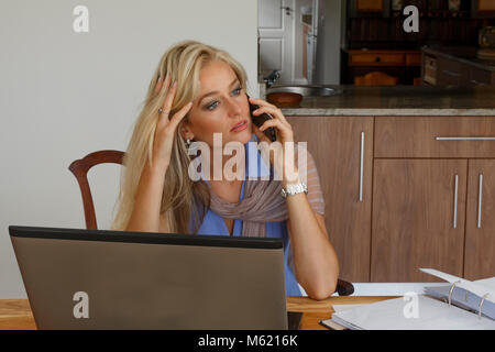 A pensive well dressed young adult woman working from home talking on a cell phone - Stock Photo